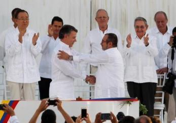 Foto del lunes del presidente de Colombia, Juan Manuel Santos (I), y el líder de las FARC, Timochenko, estrechando sus manos tras firmar el acuerdo de paz en Cartagena