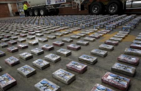 Imagen de archivo de un policía antinarcóticos vigilando unos paquetes con cocaína en una base policial en Bogotá