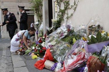 Una mujer coloca flores frente a la estación de Carabineros en la que revistaba Mario Cerciello Rega, Roma, sábado 27 de julio de 2019. Dos estadounidenses de 19 años fueron arrestados como presuntos autores de la muerte a puñaladas de Cerciello Rega. (AP Foto/Andrew Medichini)