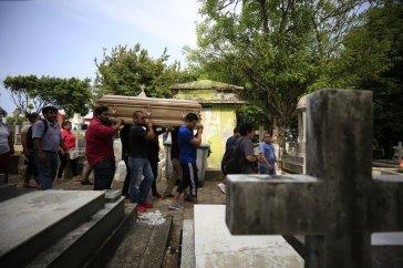 Varios hombres cargan con el féretro de Erick Hernández Enríquez, conocido como DJ Bengala, que murió en un ataque al club nocturno Caballo Blanco mientras trabajaba poniendo música, durante su entierro en el cementerio municipal de Coatzacoalcos, en el estado de Veracruz, México, el 29 de agosto de 2019. (AP Foto/Rebecca Blackwell)